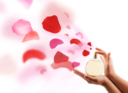 close up of woman hands spraying rose petals from beautiful perfume bottle