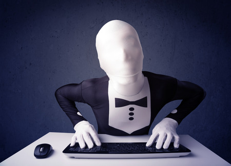 Man without identity working with keyboard and mouse on blue background photo