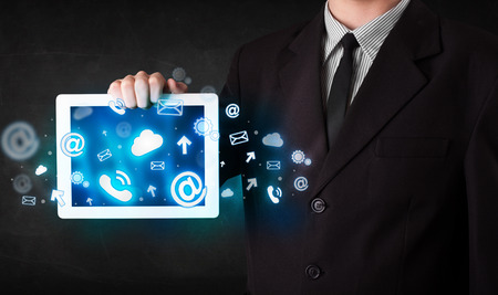 Person holding a white tablet with blue technology icons and symbols photo
