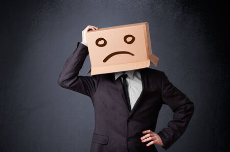 sad face: Businessman standing and gesturing with a cardboard box on his head with sad face