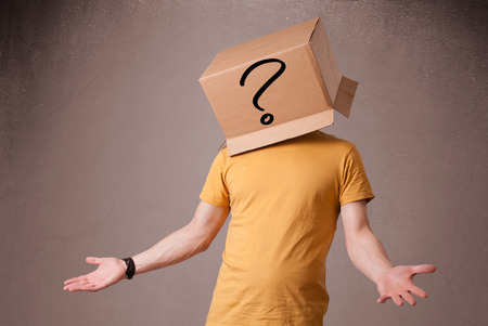 male face: Young man standing and gesturing with a cardboard box on his head with question mark Stock Photo