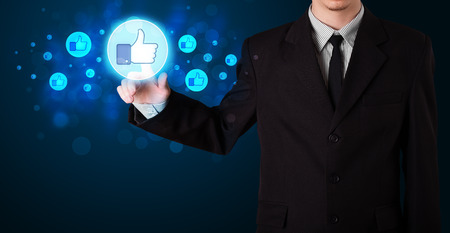 social system: Young person pressing thumbs up button on modern social network system