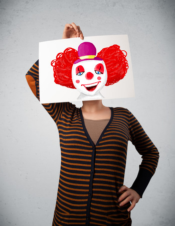 Young woman holding a cardboard with a clown on it in front of her head photo