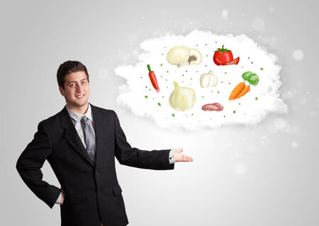 Handsome man presenting a cloud of healthy nutritional vegetables concept photo