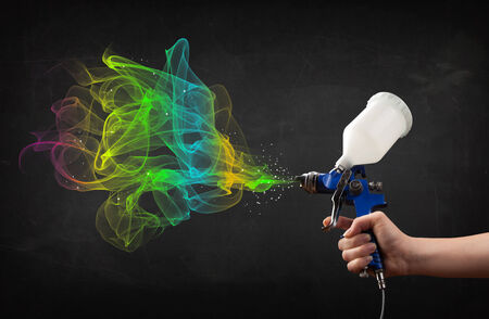 Painter working with airbrush and paints colorful paint concept photo