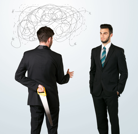 ruthless: Ruthless businessman hiding a weapon and weaving plan around his head Stock Photo