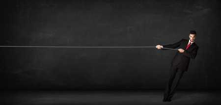 Businessman pulling rope on grey background concept photo