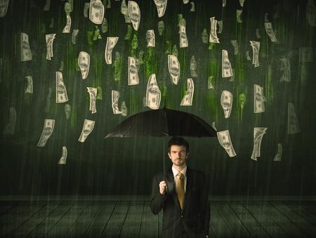 Businessman standing with umbrella in dollar bill rain concept on background photo