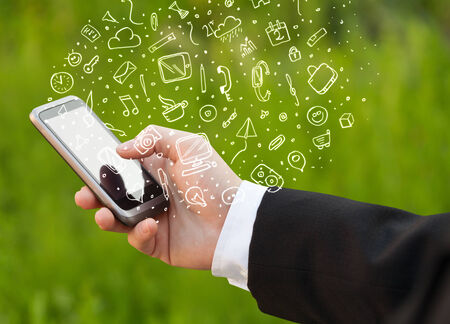 Hand holding smartphone with hand drawn media icons and symbols concept photo
