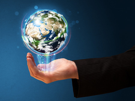 Young businessman holding in his hand a glowing earth globe  photo
