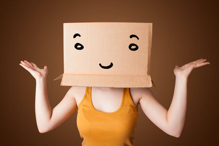 boxy: Young woman standing and gesturing with a cardboard box on her head with smiley face Stock Photo