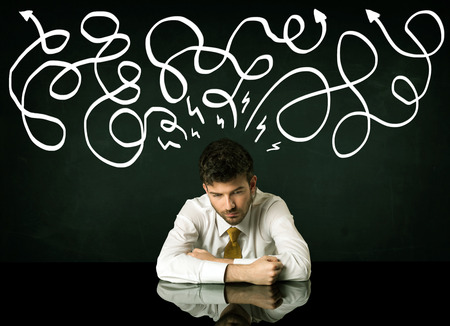 indecisive: Depressed businessman sitting under white drawn direction lines Stock Photo