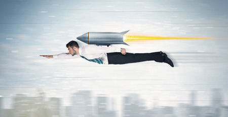 Superhero business man flying with jet pack rocket above the city concept Foto de archivo