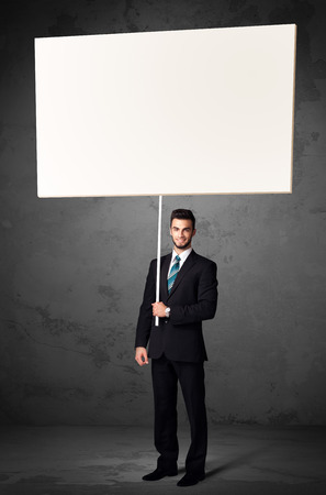 Young businessman holding a blank whiteboard photo