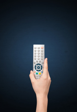 Hand holding a remote control on blue background photo