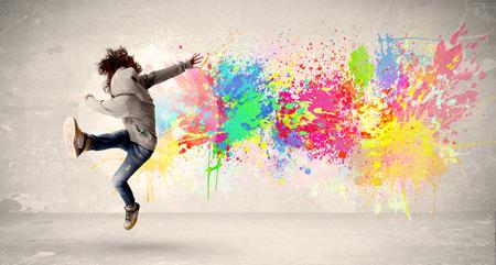 Adolescente feliz que salta con el colorido salpicaduras de tinta en concepto de fondo urbano Foto de archivo