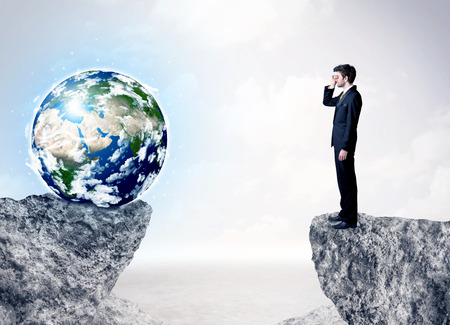 barrier free: Businessman standing on the edge of mountain with a globe on the other side Stock Photo