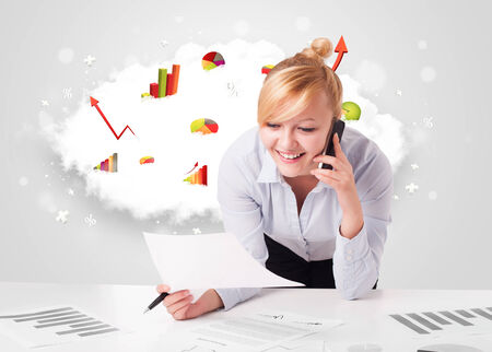 prety: Beautiful young businesswoman with cloud in the background containing colorful graphs and diagrams