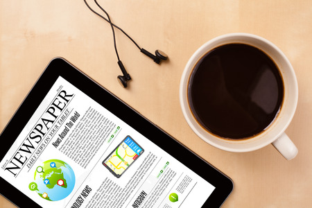 Workplace with tablet pc showing news and a cup of coffee on a wooden work table close-up photo