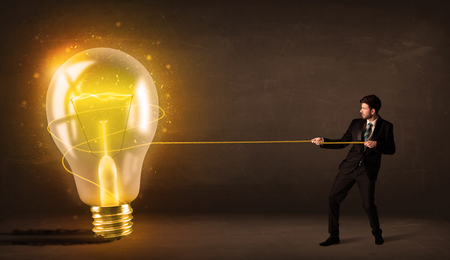 Business man pulling a big bright glowing light bulb concept on background photo