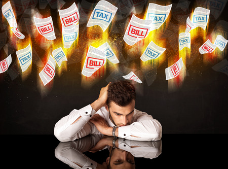 Depressed businessman sitting under falling papers photo