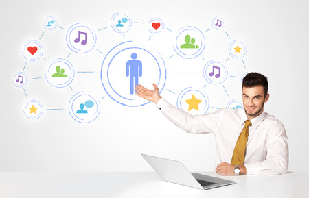 Businessman sitting at white table with social media\ connection background