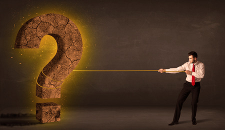 Business man pulling a big solid question mark stone concept on background photo