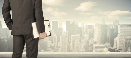 businessman suit: Businessman from the back in front of a city view on the window