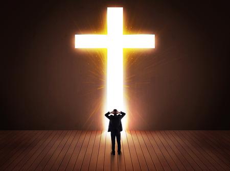 toward: Man looking at bright cross sign concept