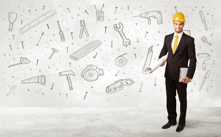 Construction worker planing with hand drawn tool icons on background photo