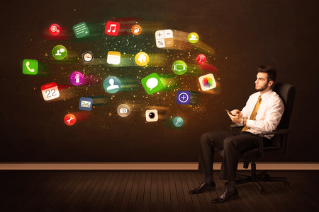 Business man sitting in office chair with tablet and colorful app icons concept on background photo