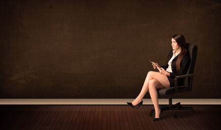 Businesswoman holding high tech tablet on brown background with copyspace photo