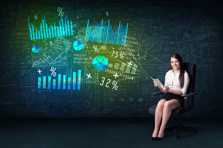 Businesswoman in office with tablet in hand and high tech graph charts concept on background photo