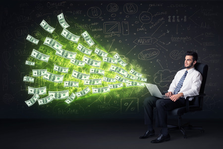 Businessman sitting in chair holding laptop with dollar bills coming out concept on background photo