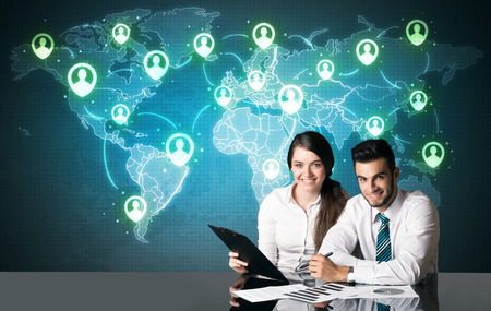 Business couple sitting at table with social media connection symbols on the world map photo