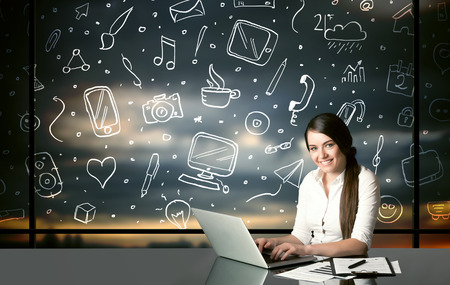 Businesswoman sitting at table with hand drawn social media icons and symbols photo
