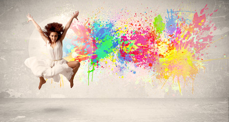 ink splatter: Happy teenager jumping with colorful ink splatter on urban background concept