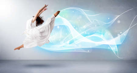 Cute teenager jumping with abstract blue scarf around her concept on background photo