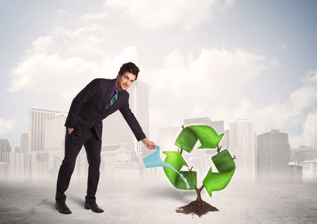 Business man watering green recycle sign tree on city background concept photo