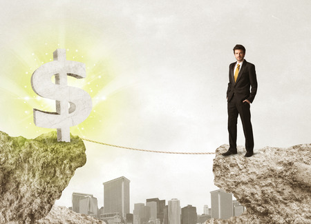 bridging the gaps: Businessman standing on the edge of mountain with a shining dollar mark on the other side