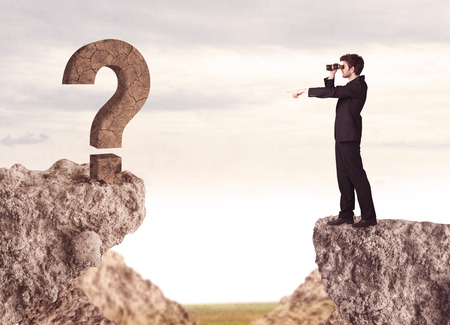 Businessman standing on the edge of mountain with a rock question mark on the other side photo