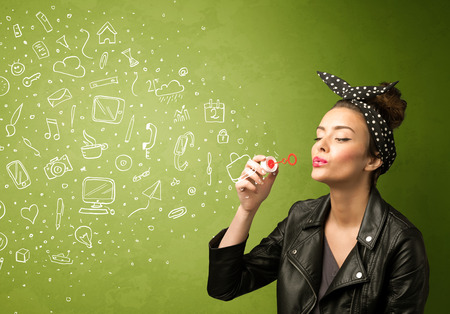Cute girl blowing hand drawn media icons and symbols on green background photo