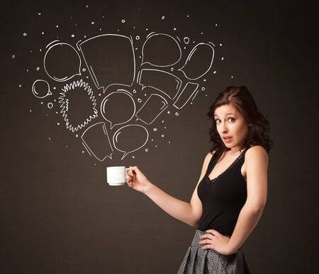 Businesswoman standing and holding a white cup with drawn speech bubbles coming out of the cup photo