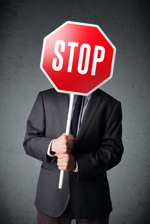 caution sign: Businessman standing and holding a stop sign in front of his head Stock Photo