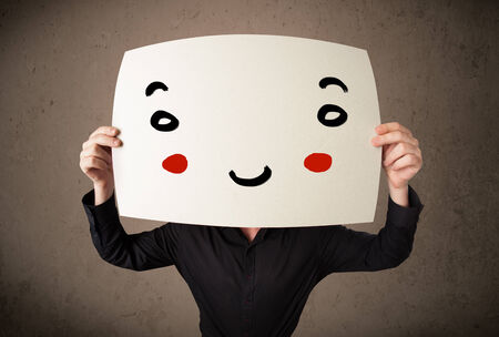 hiding face: Young businessman holding a cardboard with a smiley face on it in front of his head