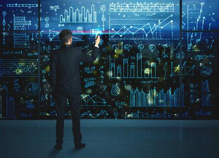 financial market: Businessman drawing business statistics on glass wall