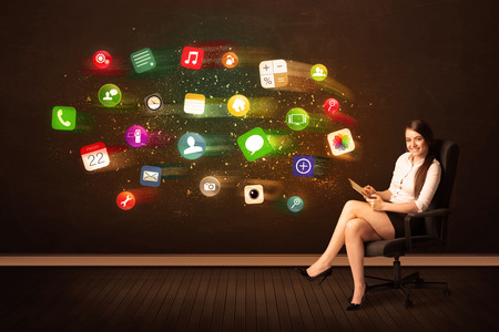 Business woman sitting in office chair with tablet and colorful app icons concept on background photo