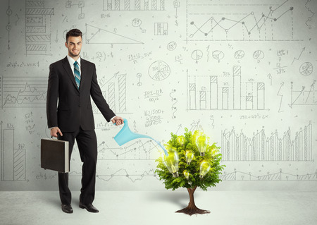 Business man pouring water on lightbulb growing tree concept photo