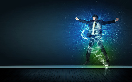 winning stock: Talented cheerful businessman jumping with glowing energy lines on background Stock Photo