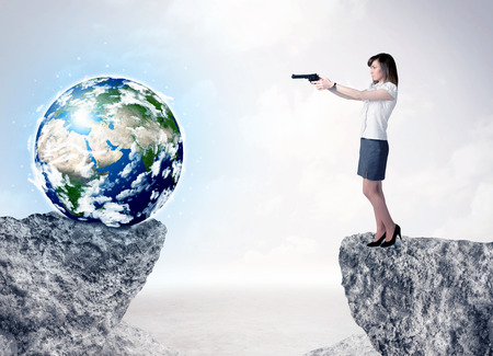 bridging the gaps: Businesswoman standing on the edge of mountain with a globe on the other side Stock Photo